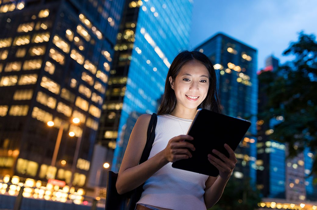 A lady using digital tablet at night