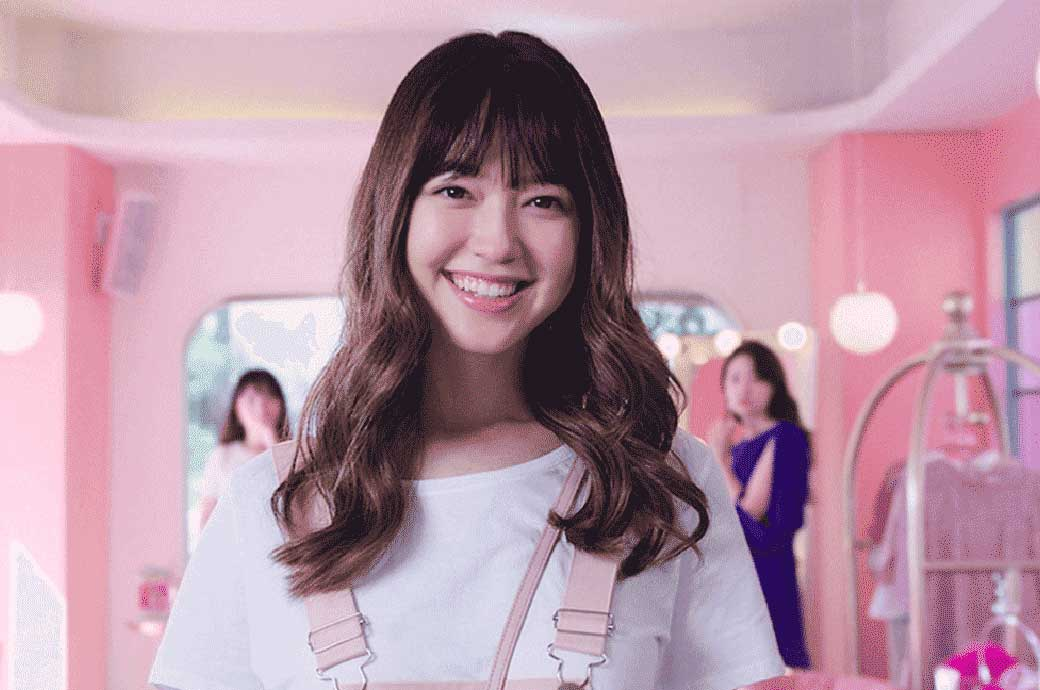 Asian girl smiling in a pink room