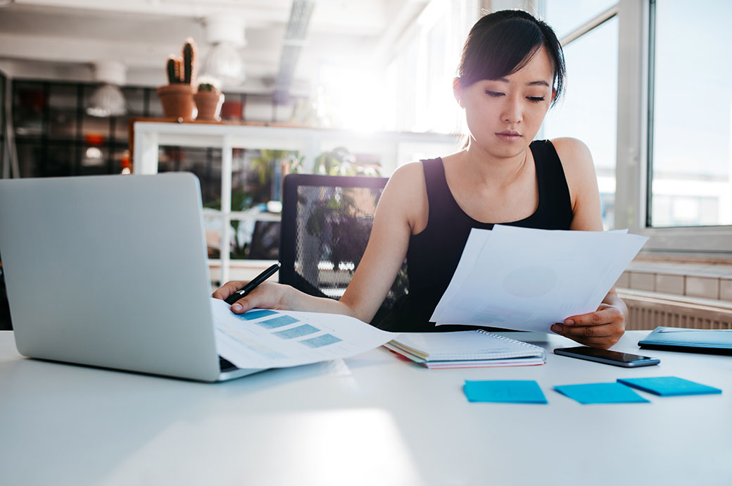 Portrait of young Asian woman reading documents at her desk. Businesswoman at her workplace doing paperwork.